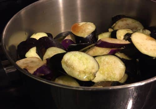 add_sliced_japanese_eggplant_to_a_pot_adding_garlic_fish_sauce_olive_oil_tomato_paste